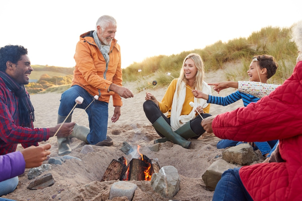 Multi-Generation Family Toasting Marshmallows Around Fire On Winter Beach Vacation